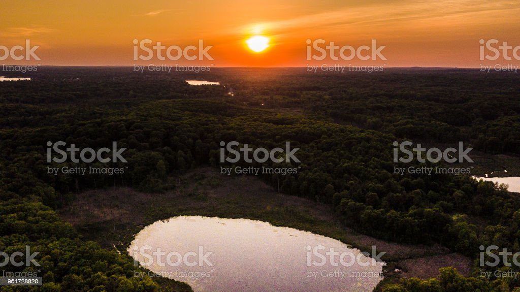 Aerial view of sunset over a small lake in the woods royalty-free stock photo