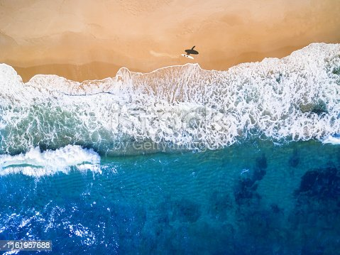 Aerial view of surfer going into the sea