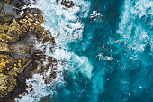 Aerial view of surfers on their surfboards.