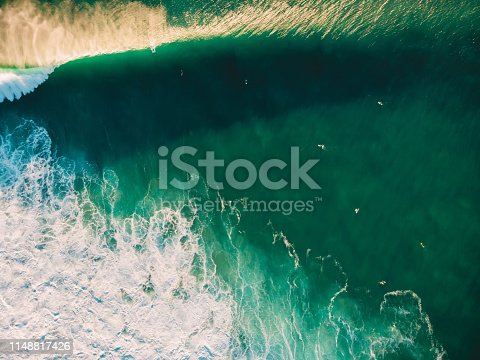 843079528istockphoto Aerial view of surfing at sunset. Surfers and big barrel wave 1148817426