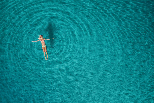 Aerial view of swimming woman in Blue Lagoon. Mediterranean sea in Oludeniz, Turkey. Summer seascape with girl, clear azure water, waves at sunrise. Transparent water.Top view from flying drone.Travel stock photo