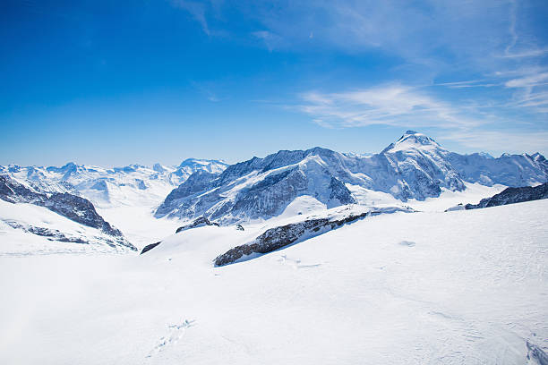 Aerial view of Swiss Alps mountains Aerial view of the Alps mountains in Switzerland. View from helicopter in Swiss Alps. Mountain tops in snow. Breathtaking view of Jungfraujoch and the UNESCO World Heritage – the Aletsch Glacier swiss alps stock pictures, royalty-free photos & images