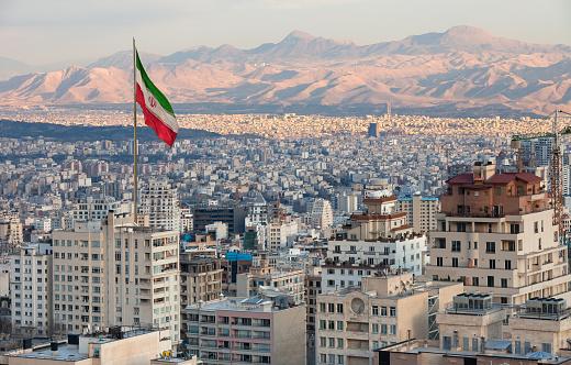 Waving Iran flag above skyline of Tehran at sunset.