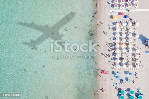 istock Aerial view of the amazing beach with the shadow of an airplane and people who swim. 1124993408