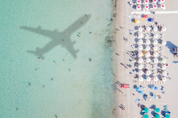 Vista aérea da praia incrível com a sombra de um avião e as pessoas que nadam. - foto de acervo