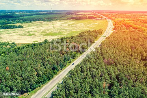 1155573645istockphoto Aerial view of the autobahn passing through the forest and fields at sunset 1006750976