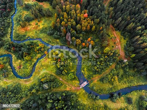Aerial view of the small river with bridge and colorful autumn forest. Russia