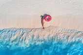 Aerial view of the beautiful young lying woman with pink donut swim ring on the white sandy beach near sea with waves at sunset. Summer holiday. Top view of slim girl, clear azure water. Indian Ocean