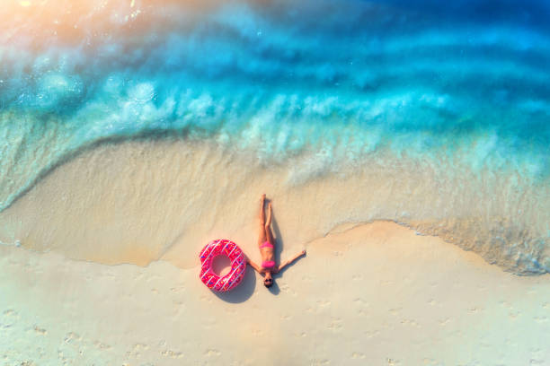 Aerial view of the beautiful young lying woman with pink donut swim ring on the white sandy beach near sea with waves at sunset. Summer holiday. Top view of slim girl, clear azure water. Indian Ocean stock photo