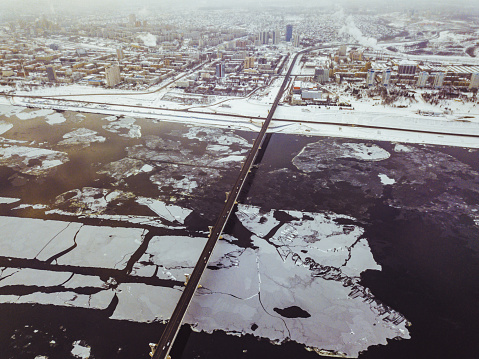 aerial view of the bridge in the city over the river during winter