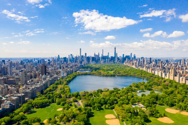 Aerial view of the Central park in New York with golf fields Aerial view of the Central park in New York with golf fields and tall skyscrapers surrounding the park. new york state stock pictures, royalty-free photos & images