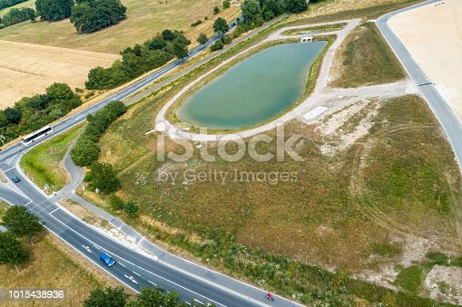 1095367134 istock photo Aerial view of the confluence of two country roads next to a new development with a rain retention basin 1015438936