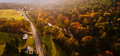 istock Aerial view of the country road in the forest in the mountain in the autumn foggy morning. 1215411102