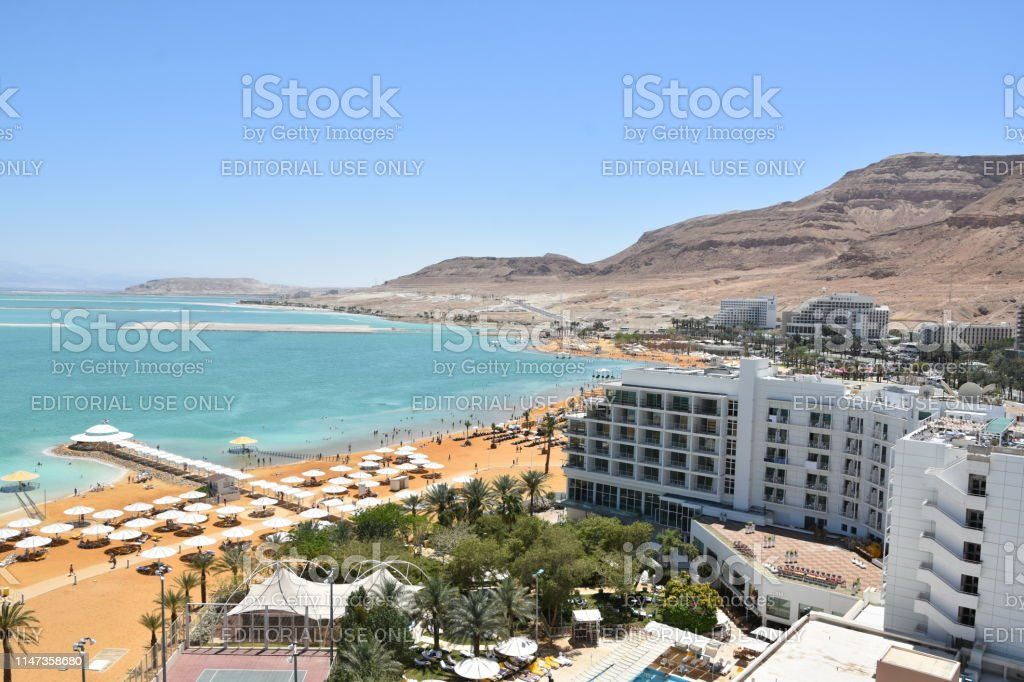 Aerial view of the Dead Sea hotels area Dead Sea, Israel: May 04, 2019:The picture shows The shoreline of the Dead Sea-  aerial view, You can see the sea, the beach,  people In the afternoon.  The Dead Sea is the lowest place in the world. The Dead Sea attracts many tourists because of its qualities that are considered to be Healthy to the body Aerial View Stock Photo