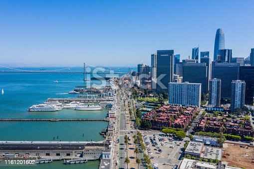 An aerial view ofthe Embarcaderor on a beautiful blue sky day. Ships, ferries and sailboats fill the San Francisco Bay.The iconic Ferry Building and Salesforce Tower surround the famous roadway.