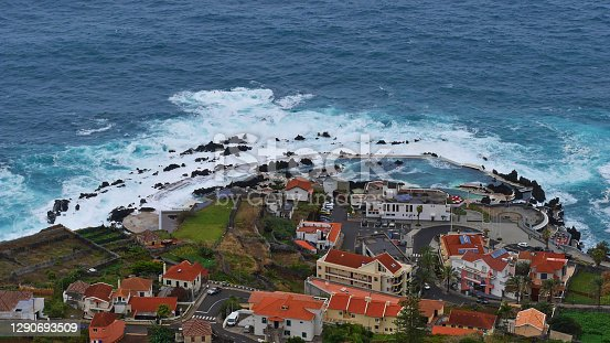 Aerial view of the famous natural swimming pools of fishing village Porto Moniz, Madeira island, Portugal flooded by the rough waves of Atlantic Ocean on stormy day.