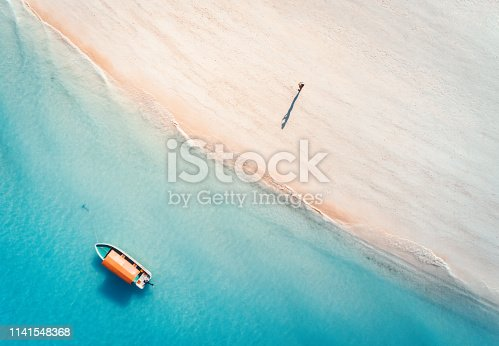 Aerial view of the fishing boat in clear blue water and man on the sandy beach at sunset in summer. Top view of boat. Indian ocean. Travel in Zanzibar, Africa. Landscape with motorboat, sea. Seascape