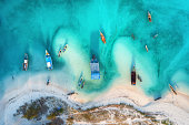 Aerial view of the fishing boats in clear azure water at sunset in summer. Top view from drone of boat, sandy beach, trees. Indian ocean. Travel in Zanzibar, Africa. Landscape with sailboats, blue sea