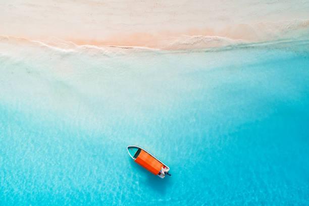 Luftaufnahme der Fischerboote in klarem blauem Wasser am sonnigen Tag im Sommer. Blick von der Drohne des Bootes, Sandstrand. Indischer Ozean in Sansibar, Afrika. Landschaft mit Segelbooten, klares Meer. Seascape – Foto
