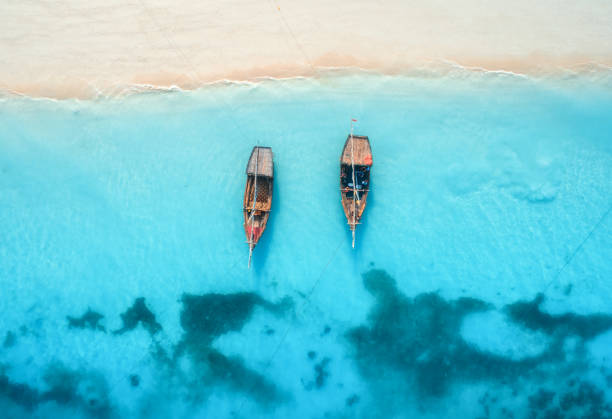 Luftaufnahme der Fischerboote in klarem blauem Wasser bei Sonnenuntergang im Sommer. Blick von der Drohne des Bootes, Sandstrand. Indischer Ozean. Reise in Sansibar, Afrika. Landschaft mit Segelbooten, Meer. Seascape – Foto