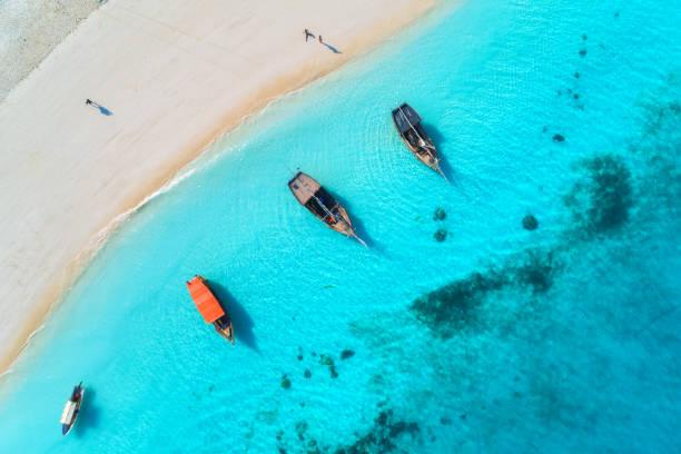 Luftaufnahme der Fischerboote in klarem blauem Wasser bei Sonnenuntergang im Sommer. Top-Ansicht von Drohne von Boot, Yacht, Sandstrand. Indischer Ozean. reise. Tropische Meereslandschaft mit Segelbooten, Meer. Blick von oben – Foto