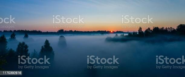 Photo of Aerial view of the forest, field and river covered with layers of thick morning fog