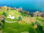 Aerial view of the golf course with blue water lake. Empty golf course top view. Aerial view of golf field with green grass. Spring, summer fresh renew life concept.