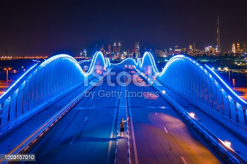 Aerial view of the Meydan Bridge and street road or path way on highway with modern architecture buildings in Dubai Downtown at night, urban city, United Arab Emirates or UAE.