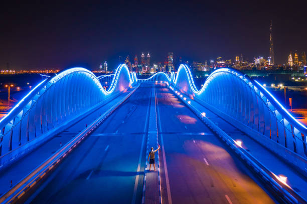 Aerial view of the Meydan Bridge and street road or path way on highway with modern architecture buildings in Dubai Downtown at night, urban city, United Arab Emirates or UAE. stock photo
