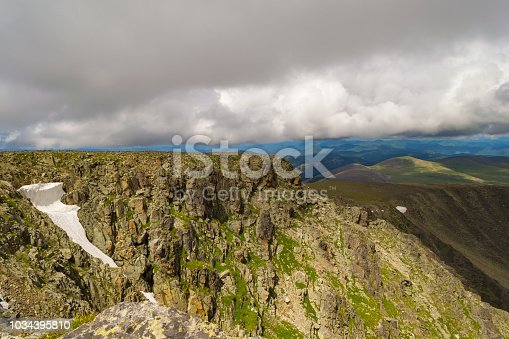 istock Aerial view of the mountain with a lot of stones and a snow glacier in the summer in the mountains of the Altai with large overhanging low gray clouds 1034395810