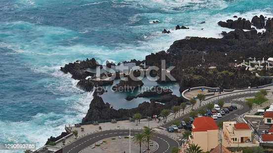 Aerial view of the natural swimming pools between rocks in small village Porto Moniz, a popular tourist destination on the northwestern coast of Madeira island, Portugal, with the wild Atlantic Ocean.