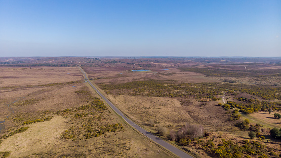 Aerial view of the New Forest National Park with heathland, road, lake and waterway under a majestic blue sky