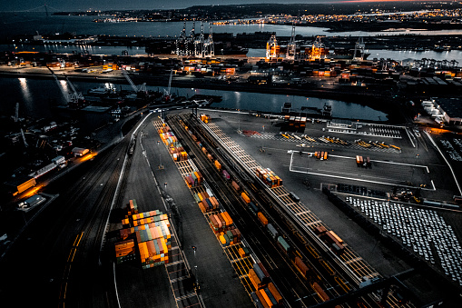 Aerial view of the New Jersey Shipyard with numerous cranes, gantries and shipping containers, captured at golden hour
