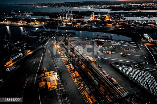 Golden hour photo of the New Jersey Dockyard in Upper Bay, New York City. Numerous cranes, gantries and shipping containers lit with street lights. Taken from a helicopter.