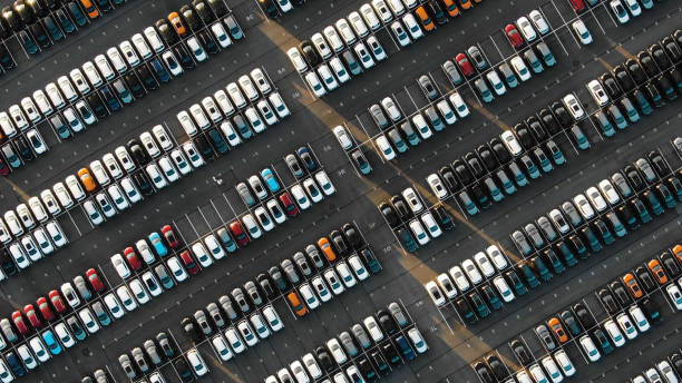 Aerial view of the parked new cars at the automotive plant fantastic flight over parked new cars at the car building enterprise at sunset, smooth rows of cars car salesperson stock pictures, royalty-free photos & images