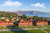 An aerial view of the Golden Gate Bridge and the Presidio. A beautiful blue sky with a hint of low fog.