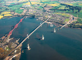 An aerial view of the construction of the new Queensferry Crossing spanning the Firth of Forth, next to the existing Victorian Forth Bridge, and the Forth Road Bridge.
