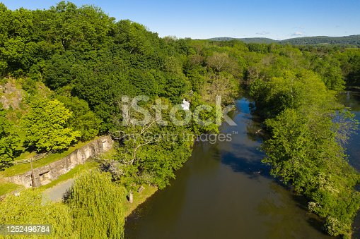 Aerial photo of the brown river water and lush greenery at the old Clinton Mill in New Jersey, USA