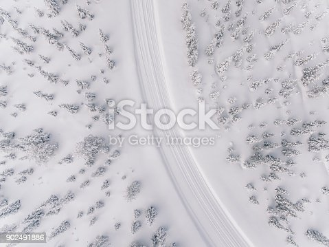 1066508460 istock photo Aerial view of the road in the winter snow forest in Finland 902491886