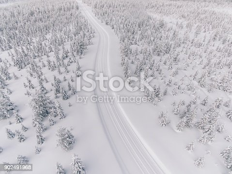 1066508460 istock photo Aerial view of the road in the winter snow forest in Finland 902491968