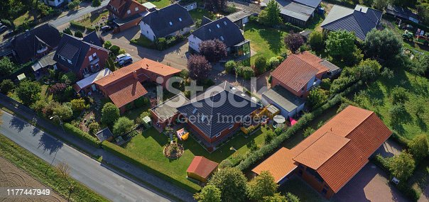 1095367134 istock photo Aerial view of the roofs of a single-family house settlement on the edge of the country road of a German suburb 1177447949