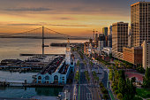 An aerial view of the San Francisco Embarcadero and famous Ferry Terminal at sunrise. Light shines off the glass skyscrapers and the street lights illuminate the street.