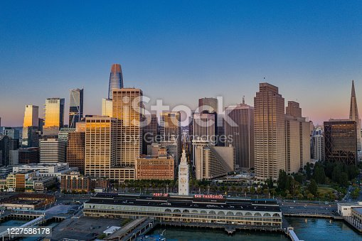 An aerial view of the San Francisco skyline look over the Ferry Terminal up Market Street. Sunrise light shines off the glass skyscrapers.