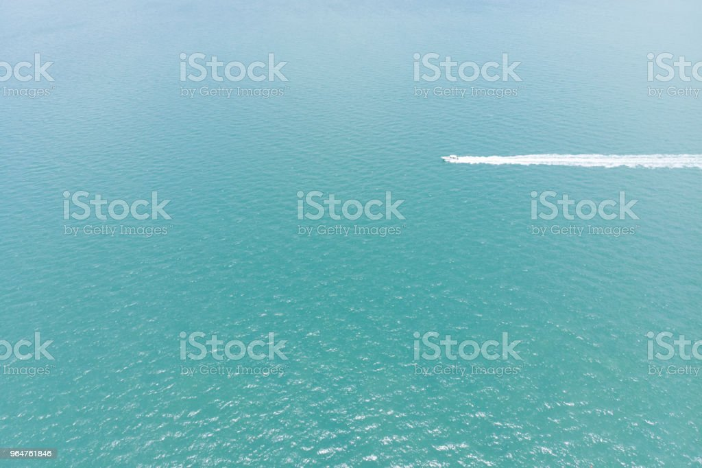 Aerial view of the sea with a motorboat crossing the ocean with white trace royalty-free stock photo