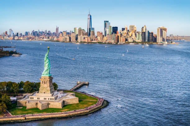 aerial view of the statue of liberty in front of Manhattan skyline. New York. USA Aerial view of Liberty island in front of Manhattan. New York. USA lower manhattan stock pictures, royalty-free photos & images