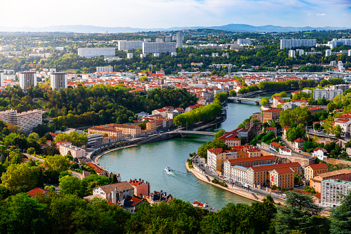 Aerial view of Lyon suburb, near Caluire and Fourviere hill, along Saone river with some residential buidings and boats sailing. Photo taken in Lyon famous city, Unesco World Heritage Site, in Rhone department, Auvergne-Rhone-Alpes region in France, Europe during a sunny summer day.
