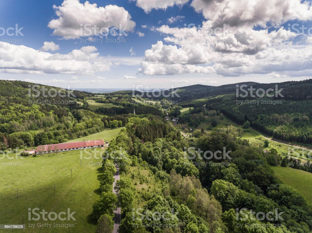 Aerial view of the summer time in mountains in border Poland and Czech Republic. Pine tree forest and clouds over blue sky. View from above. stock photo