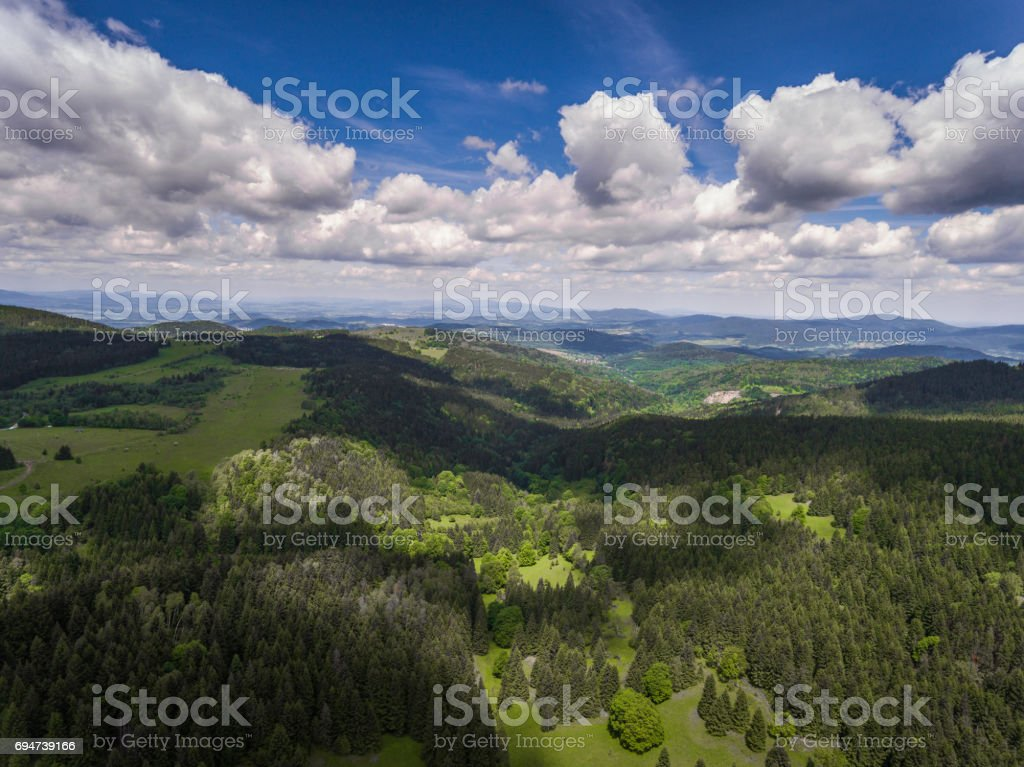 Aerial view of the summer time in mountains near Czarna Gora mountain in Poland. Pine tree forest and clouds over blue sky. View from above. stock photo