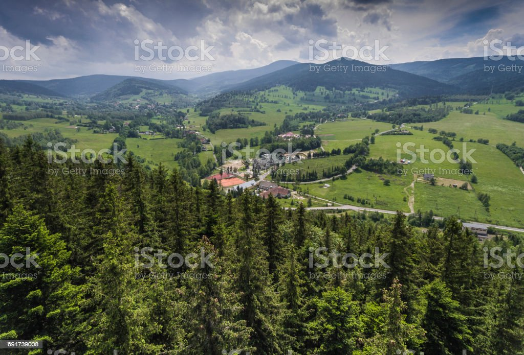 Aerial view of the summer time in mountains near Stronie Slaskie town in Poland. Pine tree forest and clouds over blue sky. View from above. stock photo