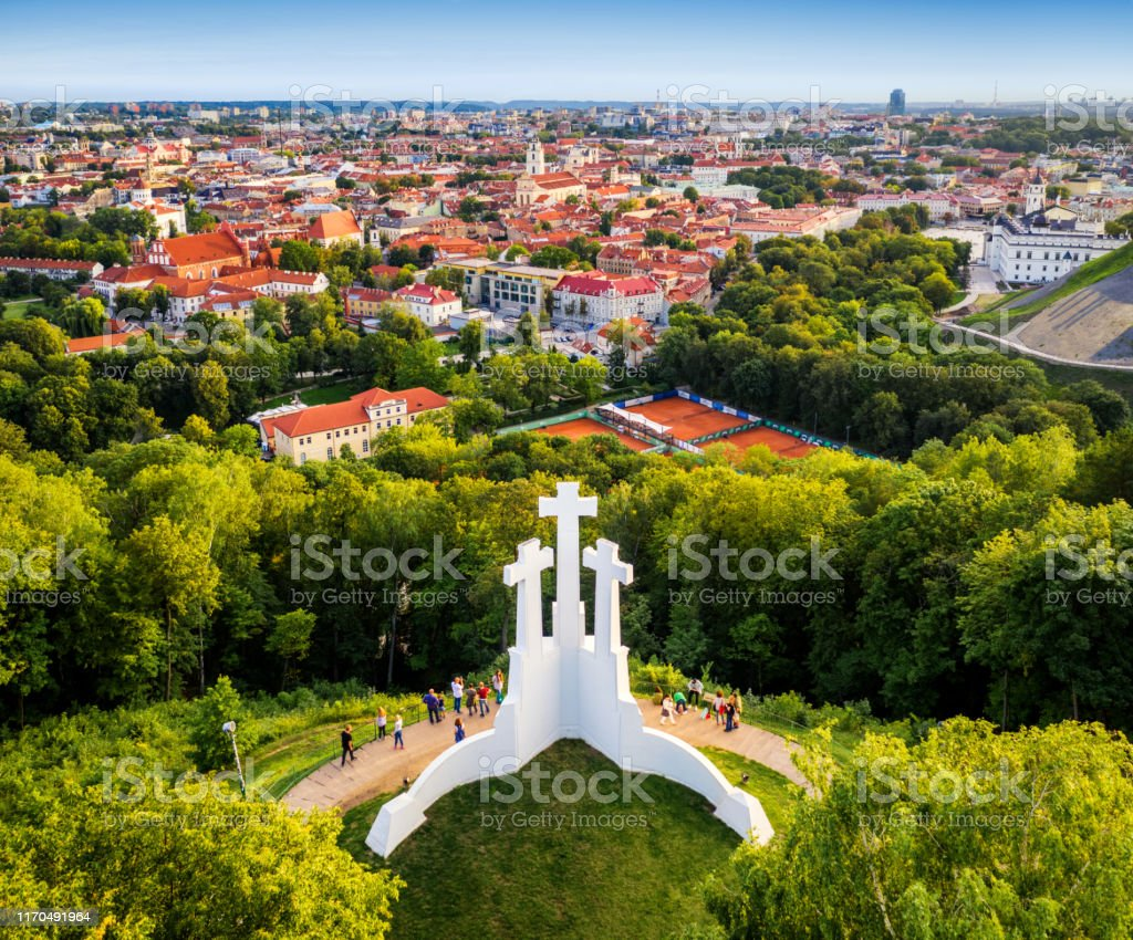 Aerial view of the Three Crosses monument overlooking Vilnius Old Town on sunset. Vilnius landscape from the Hill of Three Crosses, Lithuania Aerial view of the Three Crosses monument overlooking Vilnius Old Town on sunset. Vilnius landscape from the Hill of Three Crosses, Lithuania Aerial View Stock Photo